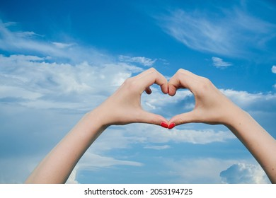 woman faceless makes heart sign with hands. Female hand with red gel polish manicure on a background of blue sky with white clouds. Copy space.