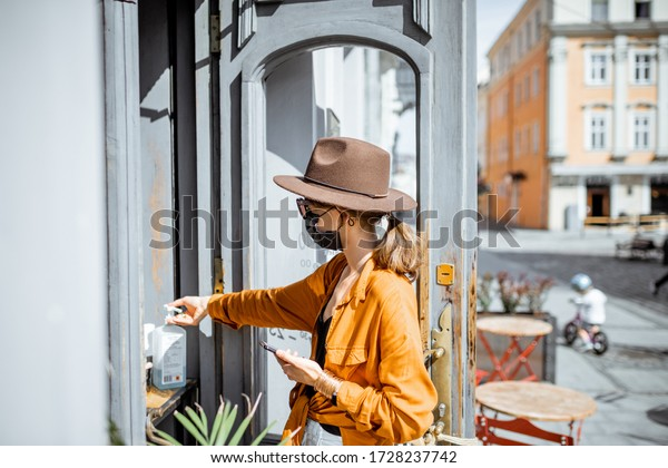 Woman in facial mask disinfecting her hands while making order for a take away food at the cafe outdoors. Concept of a new social rules after coronavirus pandemic