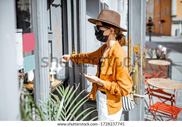 屋外のカフェで持ち帰りの注文をしながら、手を消す顔面を持つ女性。 コロナウイルスの流行後の新しい社会ルールのコンセプト