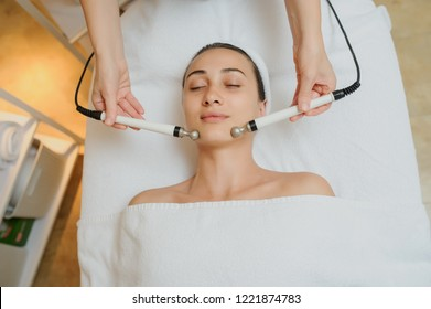Woman facial massage spa procedure. Electric stimulation facial skin care. Microcurrent lift face. Beauty spa procedure. Anti aging rejuvenation non surgical treatment in medical interior room