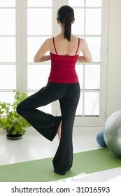 Woman facing away from camera practicing tree yoga pose at home