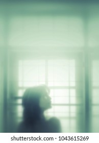 A woman facing the side Standing by the window and blurred image showing the emotions of women.