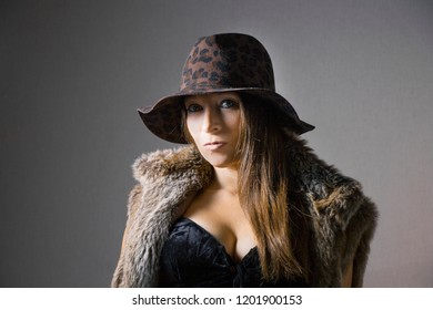 a woman in fake fur with leopard hat and big decolletage is looking straight to camera