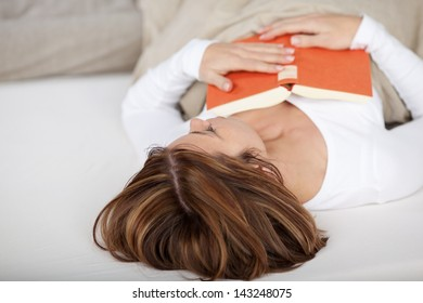 Woman fallen asleep while reading lying on her back in the bed with her book resting on her stomach