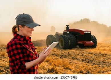 Ein Landwirt mit digitaler Tablette kontrolliert einen autonomen Traktor auf einem intelligenten Bauernhof