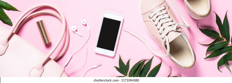Woman fashion accessories pink shoes, handbag, smartphone and lipstick on pink background. Long banner format.