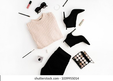 Woman fashion background concept. Sweater, jeans, shoes, sunglasses, palette, lipstick. Flat lay, top view clothes and accessories.