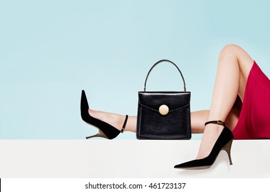 Woman fashion with beautiful black purse hand bag with high heels shoes. Copyspace on light blue background. Isolated.