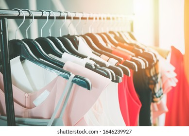 Woman fashion clothes of different colors clothing on hangers at the showroom / Hanging clothes closet rack