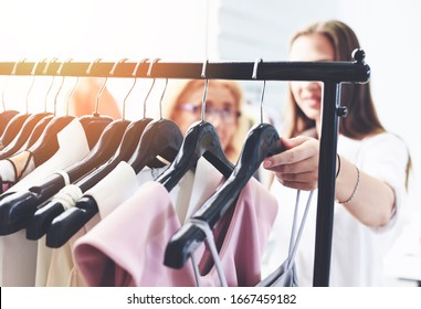 Woman fashion clothes of different colors clothing on hangers at the showroom / Shopping women choose to buy clothes hanging clothes closet rack