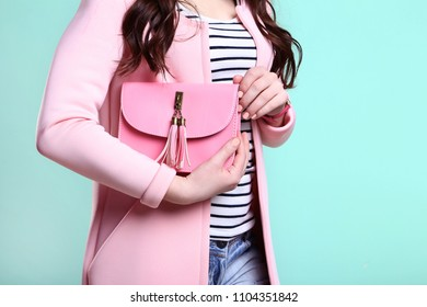 Woman in fashion clothes with handbag on mint background