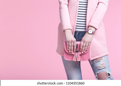 Woman in fashion clothes with handbag on pink background