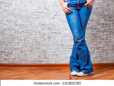 Woman fashion concept. Female legs in jeans and sneakers on gray wall background with copy space