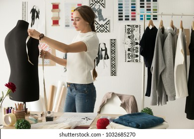 Woman fashion designer measuring mannequin, seamstress holding tape working with dummy in cozy creative design studio or tailor shop, dressmaking and sewing concept, exclusive unique clothes creation