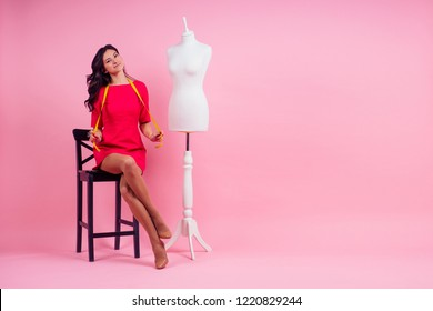 Woman fashion designer measuring mannequin attractive brunette woman seamstress tailor ( dressmaker) sitting on a chair measuring tape on a pink background in the studio