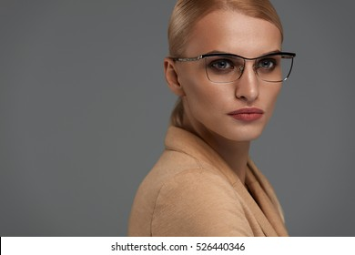Woman In Fashion Eye Glasses With Natural Face Makeup On Grey Background Portrait.