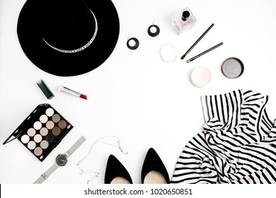 Woman fashion flatlay. Frame of modern clothes, accessories and cosmetics including a t-shirt, hat, shoes, palette, lipstick, watches, and powder on white background. Flat lay, top view.