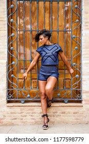 Woman fashion model posing on the grille of a large window with summer clothes.