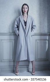 Woman fashion portrait in the gray maxi coat