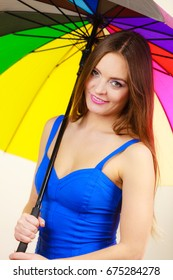 Woman fashion summer attractive girl wearing blue dress standing under colorful rainbow umbrella, on gray. Positive smiling female model. Forecasting and weather season concept