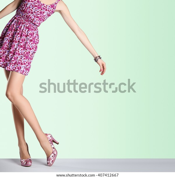 Woman in fashion sundress and high heels. Female sexy long legs, model pose, stylish pink floral dress. Unusual creative elegant sexy girl. Lady outfit