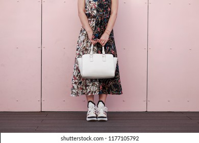 Woman in a fashionable dress with a white stylish bag stand near the pink wall. Women's Fashion Sneakers