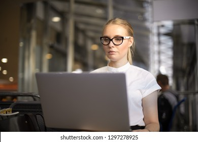 Woman in fashionable glasses professional economist reading financial news on web site via laptop computer while sitting in corridor of modern company interior. Female student online learning