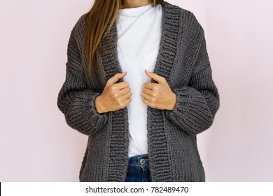 woman in fashionable gray knitted cardigan stands against the background of a pink wall