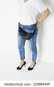 Woman in fashionable jeans, heels and fanny pack
