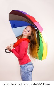 Woman fashionable rainy smiling girl in red clothing standing under colorful umbrella having fun. Meteorology, forecasting and weather season concept