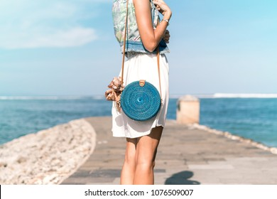 Woman with fashionable stylish blue rattan bag and silk scarf outside. Tropical island of Bali, Indonesia. Rattan handbag and silk scarf.
