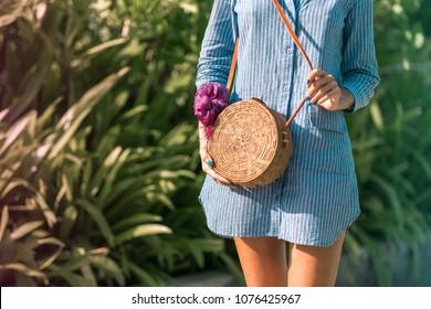 Woman with fashionable stylish rattan bag and silk scarf outside. Tropical island of Bali, Indonesia. Rattan handbag and silk scarf.