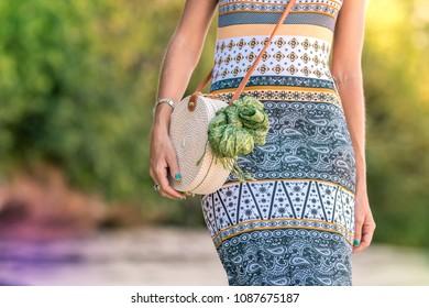 Woman with fashionable stylish rattan bag outside. Tropical island of Bali, Indonesia. Rattan and silk.