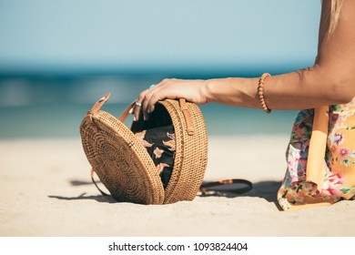 Woman with fashionable stylish rattan bag and silk scarf outside. Tropical island of Bali, Indonesia. Rattan handbag and silk scarf.