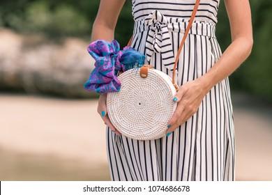 Woman with fashionable stylish white rattan bag and silk scarf outside. Tropical island of Bali, Indonesia. Rattan handbag and silk scarf.