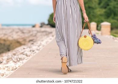 Woman with fashionable stylish yellow rattan bag and silk scarf outside. Tropical island of Bali, Indonesia. Rattan handbag and silk scarf.