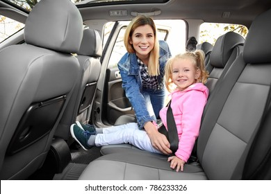 Woman fastening security belt on her little daughter in car