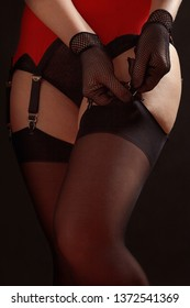 Woman fastens black stockings to the erotic garter belt on a black background close up