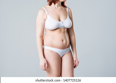 Woman with fat flabby belly, overweight female body on gray background, studio shot