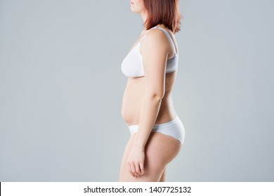 Woman with fat flabby belly, overweight female body on gray background, side view