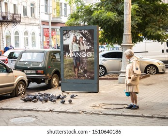 The woman fed the pigeons and watches them eat. Odessa City, Ukraine, September 2019