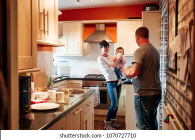 Woman is feeding the baby with a bottle while talking to her husband in the kitchen of their home.