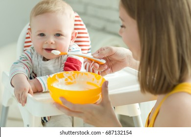 A woman is feeding a child