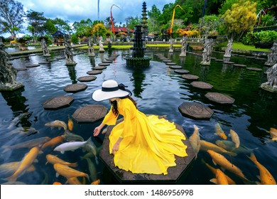Woman feeding colorful fish in pond at Tirta Gangga Water Palace in Bali, Indonesia.