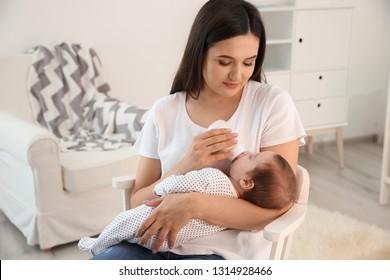 Woman feeding her baby from bottle in nursery at home