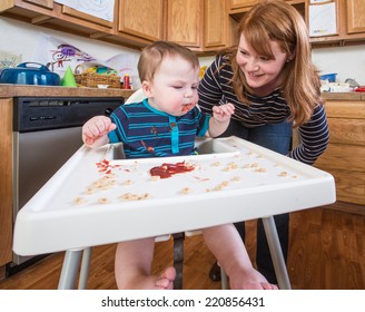 A woman feeds her baby breakfast in the kitchen