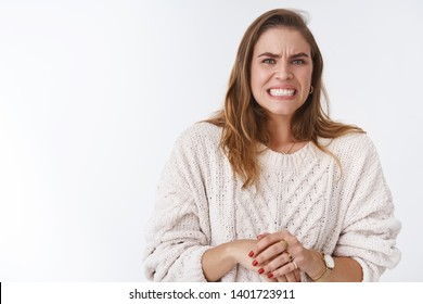 Woman feeling awkward intense feeling problems, making huge mistake worrying grimacing wrinkle nose clenching teeth stooping guilty, nervously touching hands, standing insecure white background