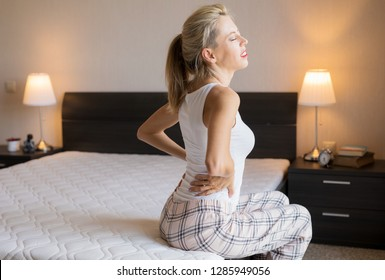 Woman feeling back pain after sleeping in bed at home
