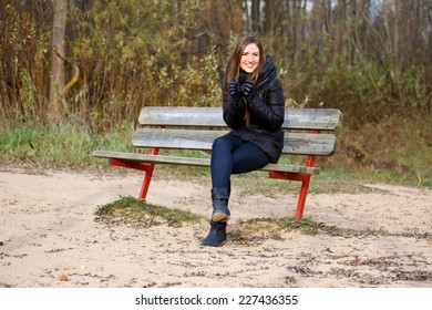 Woman feeling cold on beach bench