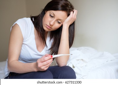 Woman feeling depressed and sad after looking at pregnancy test result